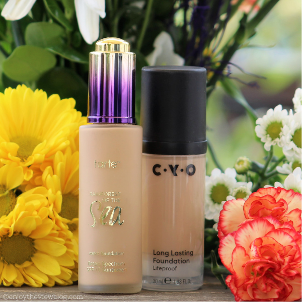 two bottle of liquid foundation makeup sitting in front of yellow and orange flowers
