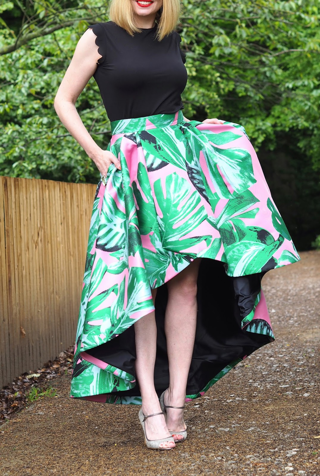 Asymmetric hem statement  summer skirt, pink and black with large leaves, champagne glitter Jimmy Choo sandals, occasionwear, black scalloped sleeve top