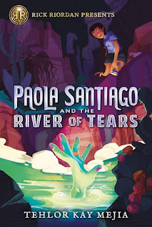 A young girl in a purple t-shirt is on the edge of a rocky riverbed, looking down into glowing green water, where a large green hand made of water is reaching up as if to grab her.