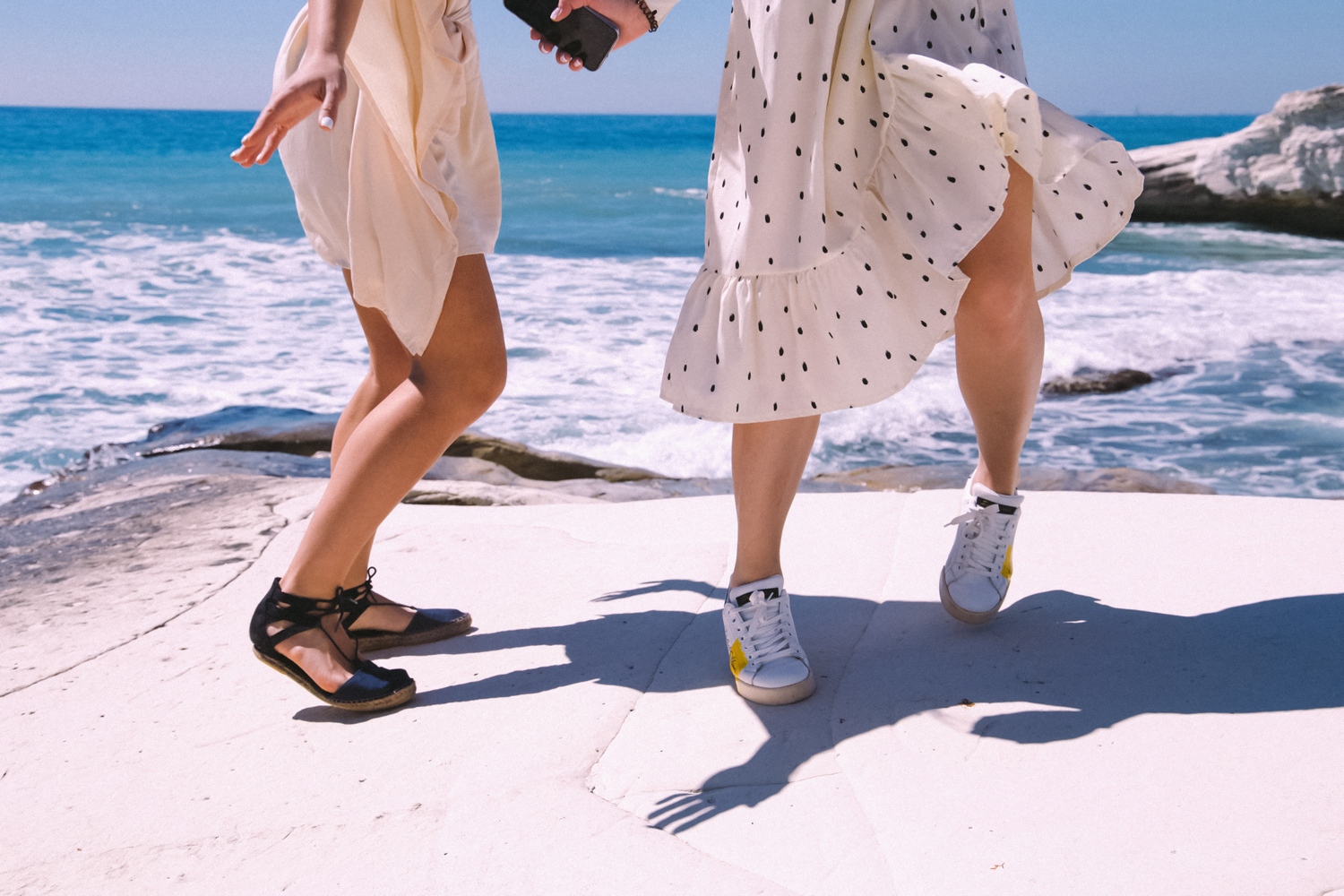 two girls in skirts and sandals are playing on the sunny beach