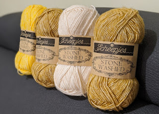 Four balls of Stone Washed Scheepjes yarn lined up together.