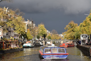 Dark storm clouds beyond a sunlit canal, Amsterdam, The Netherlands