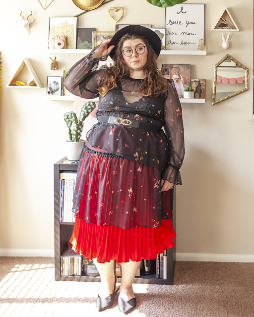 An outfit consisting of a sheer black ling sleeve dress with asymmetrical layers, layered over a black lace bralette and red pleated midi skirt and black pointed toe slingback flats.