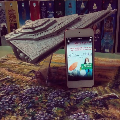 A white iPod leans up against a speaker shaped like a Star Destroyer. Its screen shows the cover of A Corner of White, featuring a brunette white girl holding a gleaming white piece of paper up to her face as an orange umbrella blows by in the background. Underneath the speaker and the iPod is a puzzle consisting mainly of horrid purple grapes still on the vine.