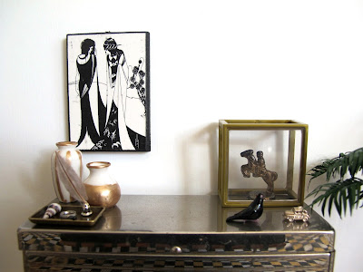 Art deco style modern miniature silver sideboard with a selection of white, black and gold-coloured items displayed on it.