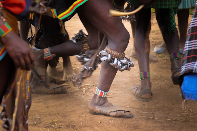 silver bells on the leg of a bena girl dancing during the bull-jumping ceremony in omo valley, ethiopia