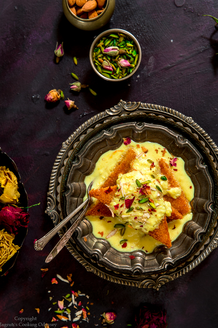Light yellow colour Shahi Tukda served in a vintage metal bowl garnished with pistachio slivers, rose petals with a spoon.