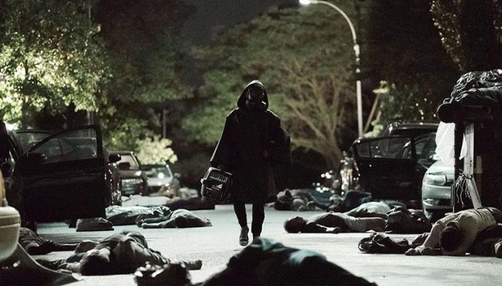 O fundo é uma rua devastada cheia de pessoas mortas no chão e carros abertos e esta noite e no centro da imagem tem uma figura encapuzada caminhando com uma casa transportadora  de animais domésticos na mão.