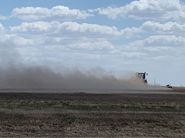 Photo showing a tractor pulling a soil tillage implement and causing soil to blow away.