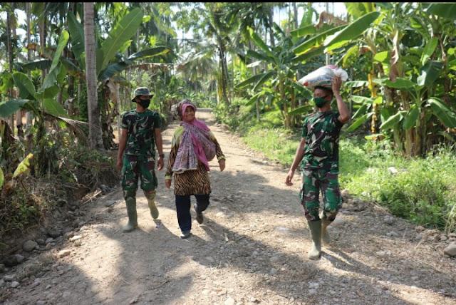 Nenek Tersenyum , Saat Anggota TNI Satgas TMMD Membantu Mengangkat Barang Bawaanya