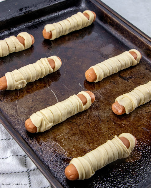 Hot dog wrapped in crescent roll strips to make a mummy lined up on baking sheet