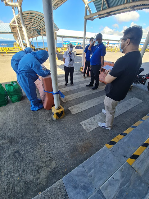 Joining seafarers in full PPE crew change filling up forms at Batangas Port