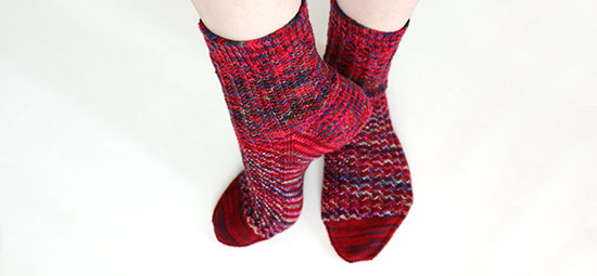 Feet casually posed wearing hand knit socks in shades of red with hints of other colors, on a white background.