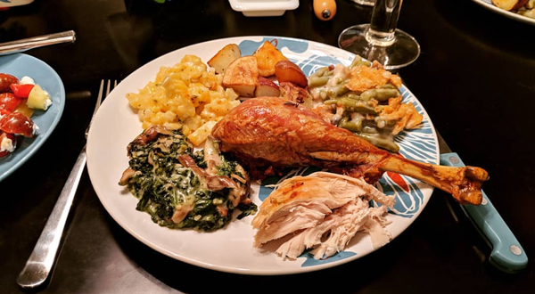 image of a plate with a turkey drumstick, some sliced turkey breast, and a few side dishes