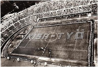 """Postikortti, jonka Eero lähetti isälleen Helsingistä juhannuksena 1954. Kuvattu Stadionin tornista - voimistelijat ovat muodostaneet tekstin """"KISA - TYÖ""""."""