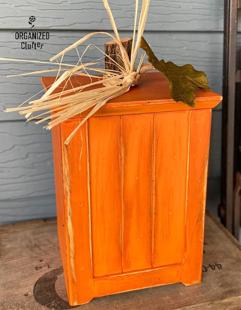 Photo of a wooden canister repurposed as a fall pumpkin