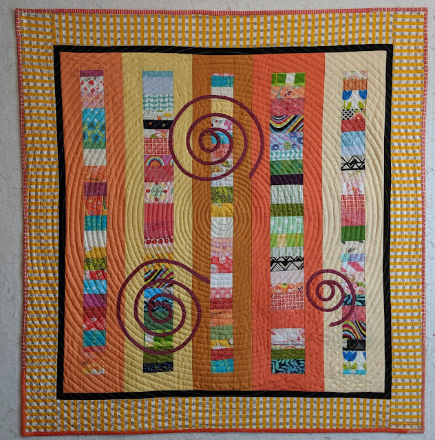 Narrow Chinese Coins are sashed with soft tints of yellow and orange solids. A narrow black inner border and a wide yellow and white stripe frame the quilt. Three spirals of magenta shot cotton are  appliqued on the surface.