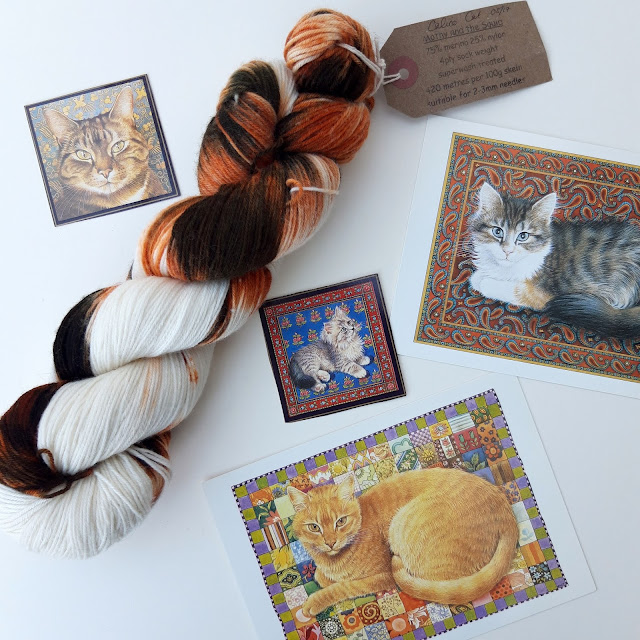 A flatlay showing a calico cat-coloured skein of yarn surrounded by pictures of cats