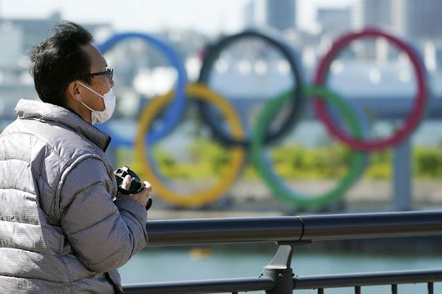 Homem usando máscara incorretamente tira foto perto dos anéis olímpicos em Tóquio, no distrito de Odaiba — Foto: Eugene Hoshiko/AP
