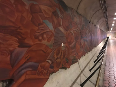 View down the Metro entrance tunnel showing a mural running the length of the wall.