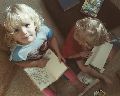 Toddler reading upside down book