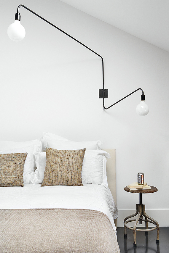 High-impact things to hang over your headboard | Oversized swing arm wall sconce. Via AD