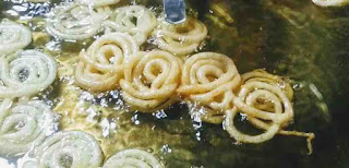 Crisp golden jalebi frying on oil