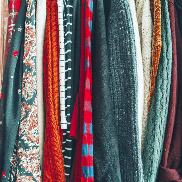 A flatlay of row of hanging sweaters and blouses.