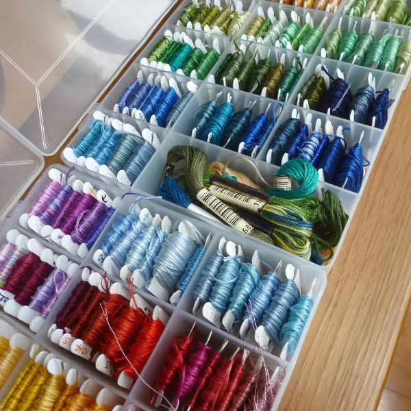 Lots of colors of embroidery floss organized into storage boxes ready for sewing