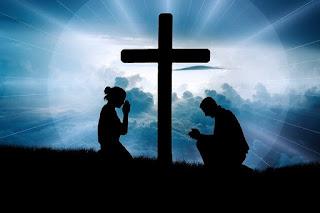 Duas pessoas orando aos pés da cruz com luz