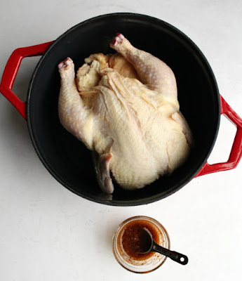 whole chicken in dutch oven with small bowl of oil and spices nearby to go on chicken