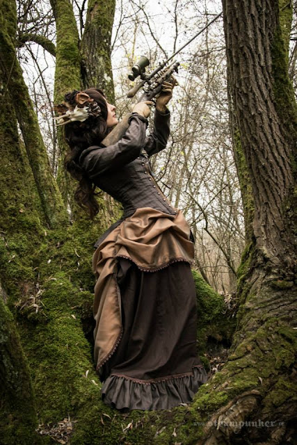 Woman in steampunk victorian clothing with a steampunk gun. Brown steampunk dress/victorian clothing for women