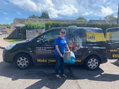 Cats Protection female volunteer standing next to Cats Protection van holding cat carrier