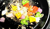 Stir frying onion capsicum red yellow bell peppers for chilli chicken gravy