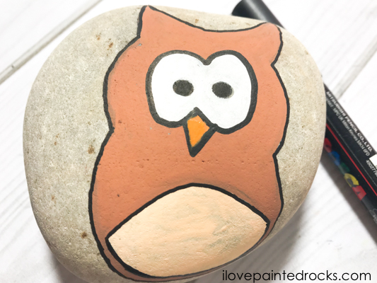 colour the owls beak orange using acrylic paint or a posca pen to create your owl painted rock