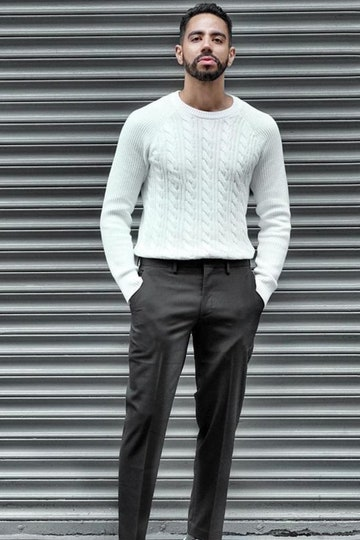 Men's street style: white knitted sweater with men's trousers posing