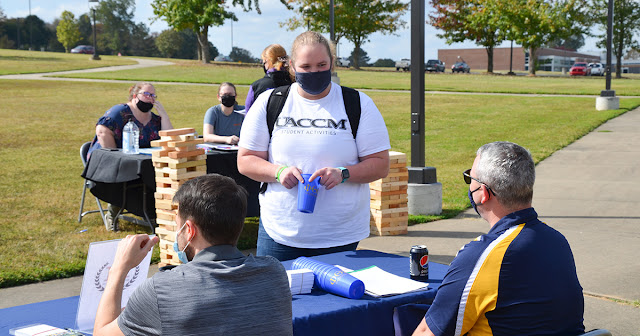 student stands at a booth to speak to student organization representatives