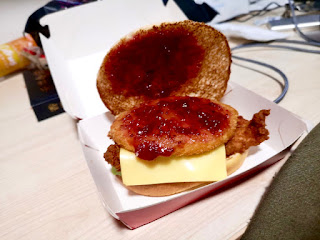 A large circular light brown chicken burger with dark red cranberry sauce and white may with yellow cheese and golden brown hash brown between two golden brown bread buns in a white box on a light brown rectangular table on a bright background