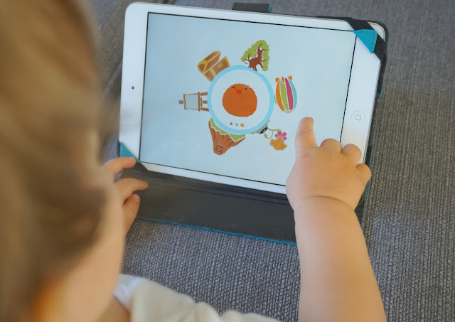 close up of toddler boy playing on an ipad