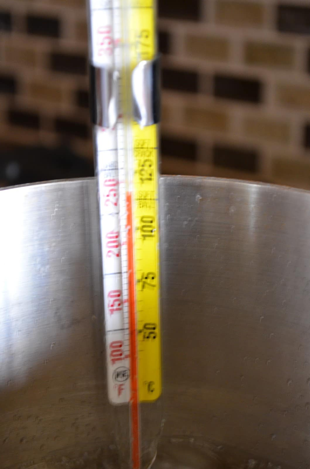 Candy Thermometer at 250 degrees attached to the side of pan in boiling sugar.