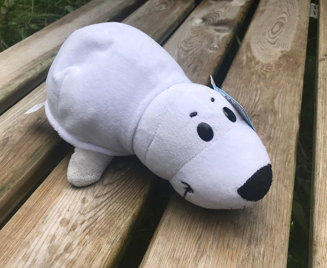 white seal plush toy on a bench in garden