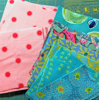 Several turquoise print choices next to a pink fabric with large red polka dots
