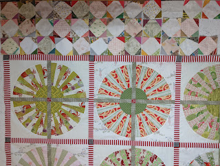 This version of the snowball borders has corners that closely match the colors and values of the Wheel blocks in the center of the quilt
