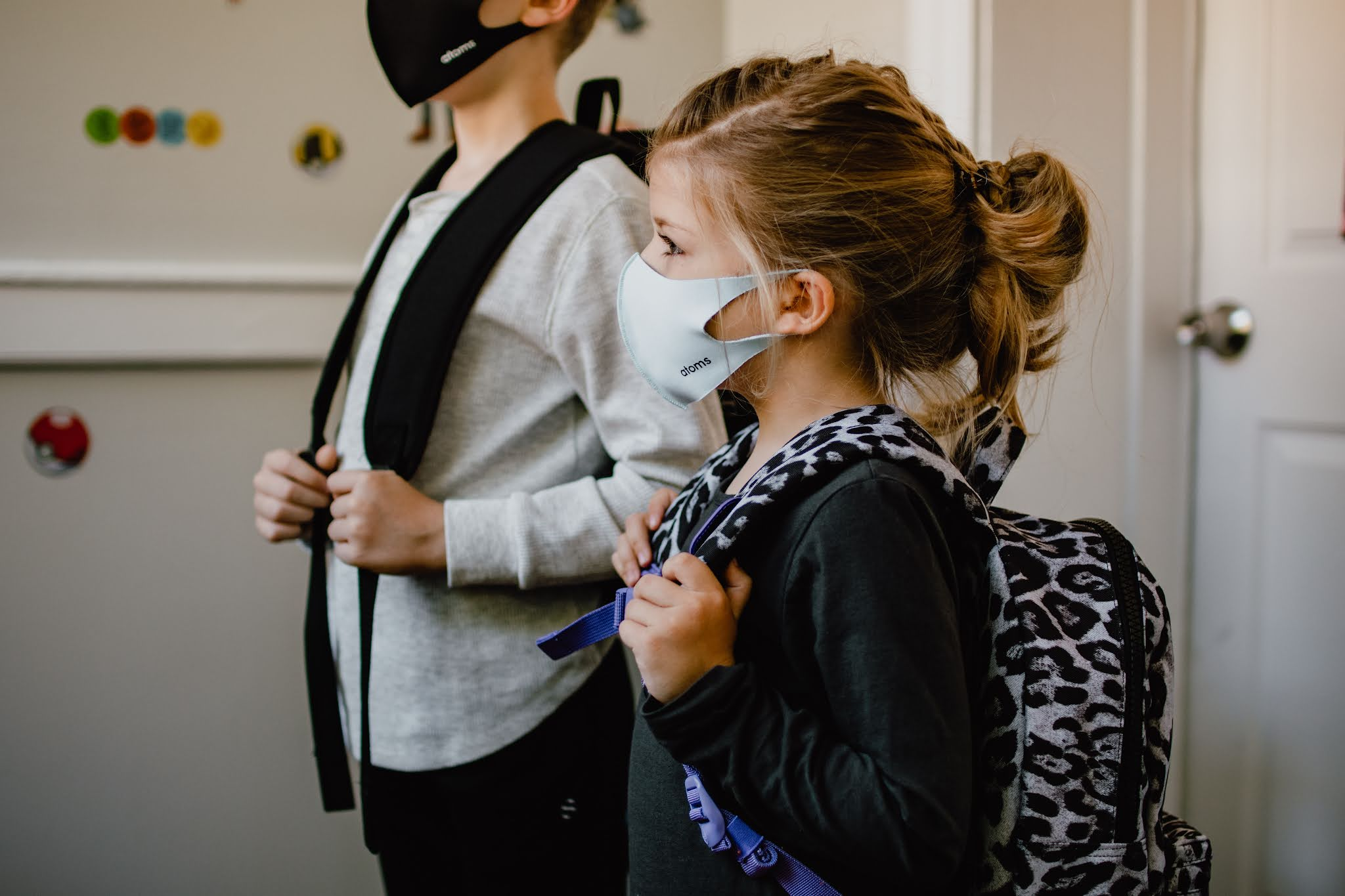 2 children wearing backpacks and facemasks