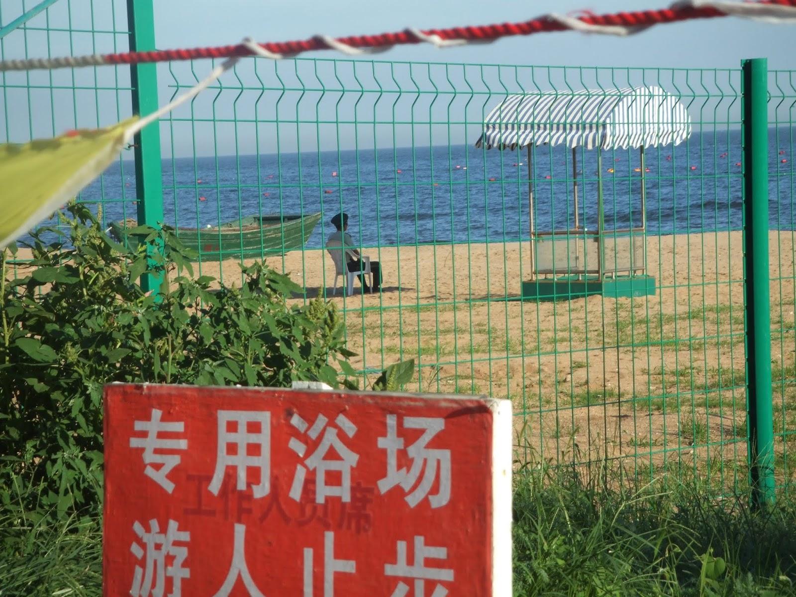 Mann in Uniform hinter grünem Zaun neben grünem Boot am Strand