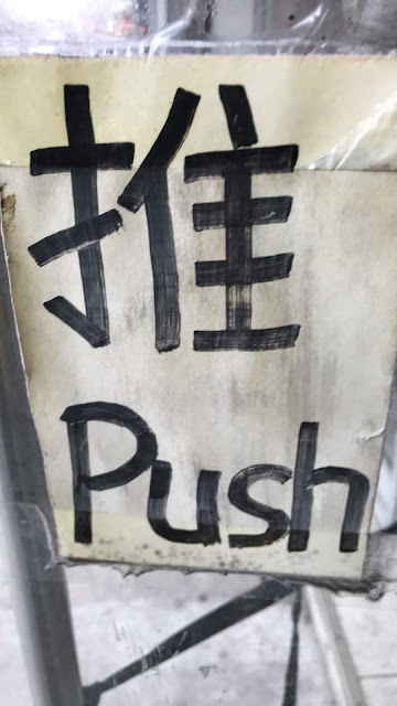 "A storefront door has a sign affixed to it in Mandarin Chinese and in English for ""Push"""