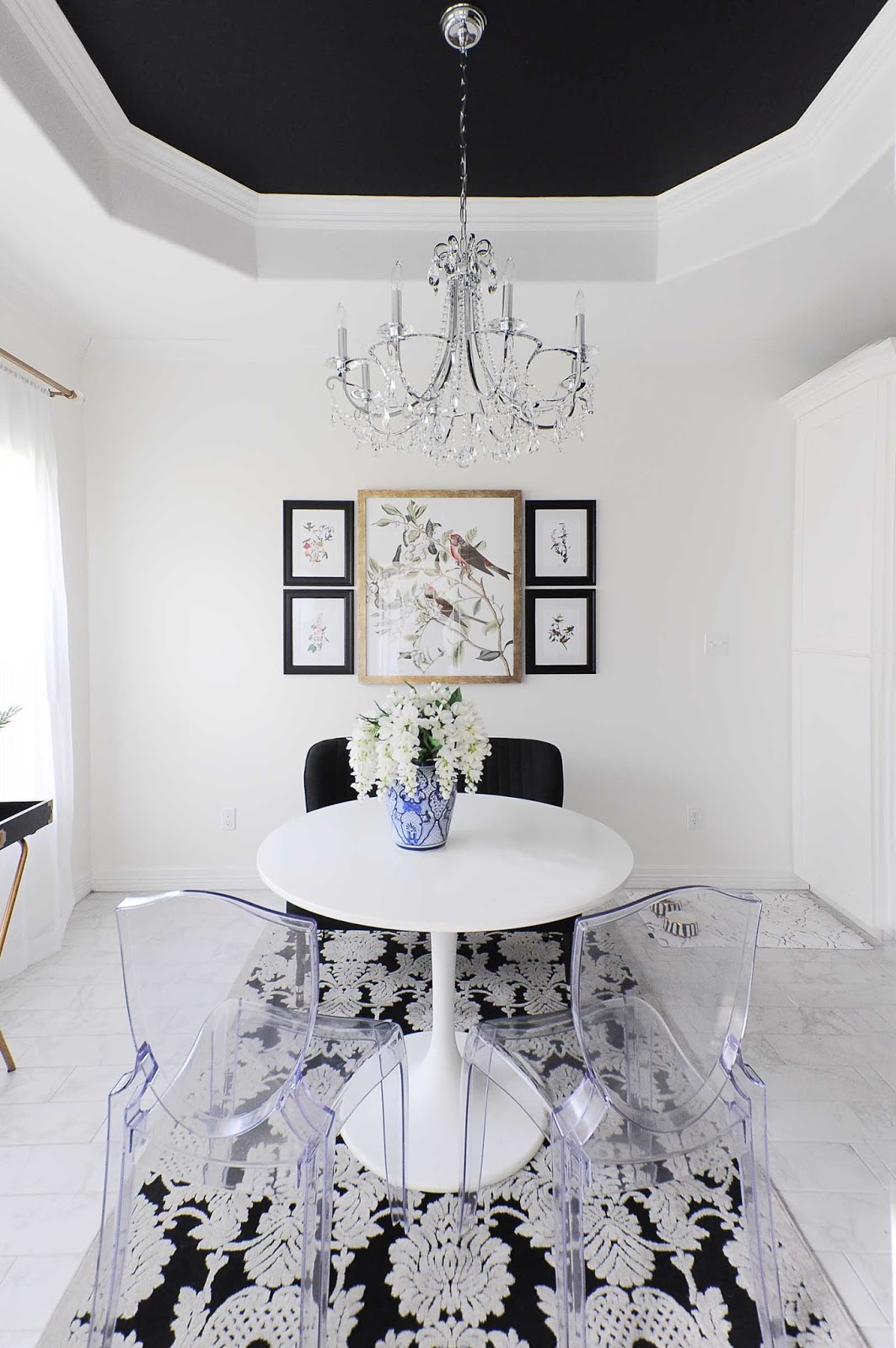 A black tray ceiling and crystal chandelier make a dramatic statement in a small dining room space with floral, audubon and chinoiserie touches.