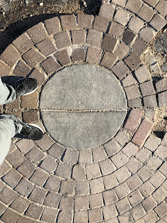 feet next to a concrete and brick marker