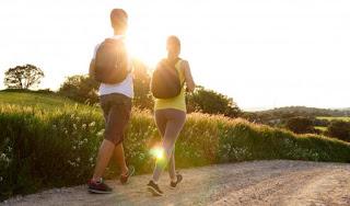 casal caminhando em frente ao pôr do sol