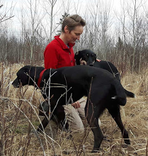 Kristi Benson, writer and dog trainer, pictured in a field with two dogs